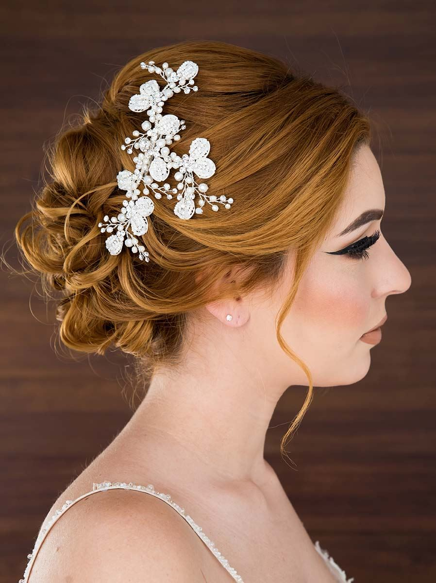 Model wearing white wedding dress and floral hairclip