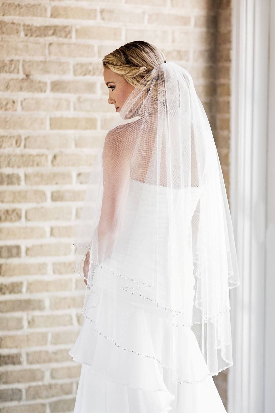 Model wearing white wedding dress and veil