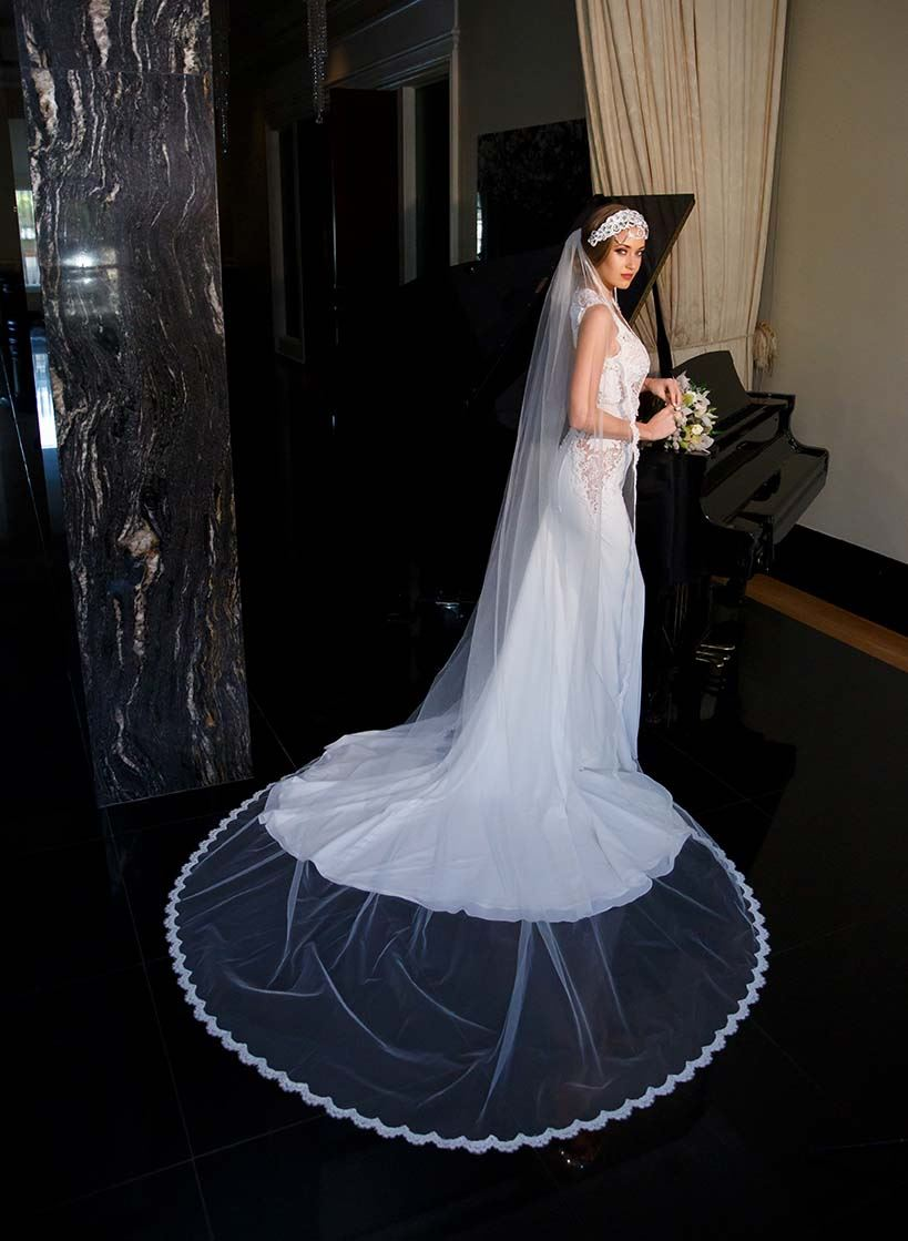 Model wearing white wedding dress and veil while holding bouquet